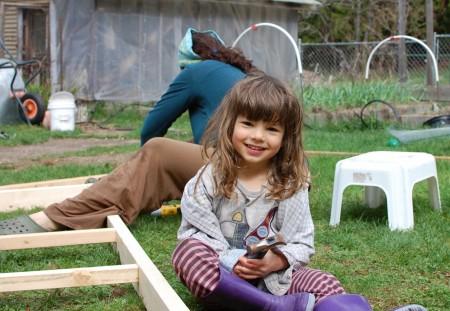 טל עוזר לאמא בבניית עוד מסגרת עשב לתרנגולות.